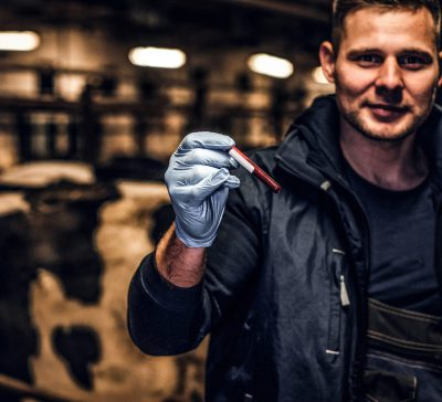 Vet holding a sample in a cattle shed - TB Hub